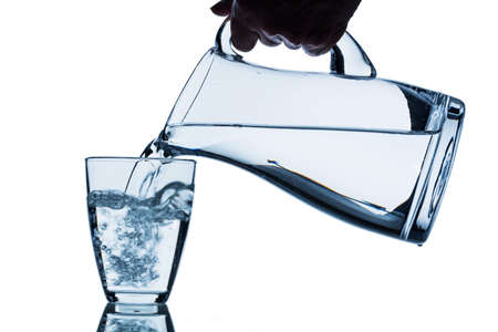 emptied: pure water is emptied into a glass of water from a pitcher. fresh drinking water