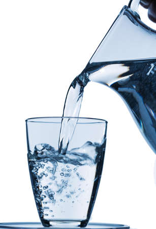 dehydrate: pure water is emptied into a glass of water from a pitcher. fresh drinking water