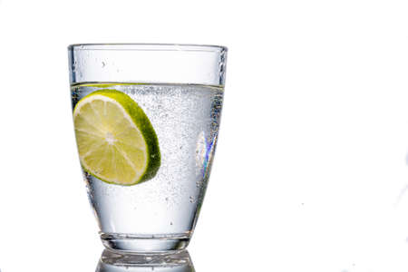 a glass of fresh drinking water and a lime. mineral water as a thirst quencher. photo