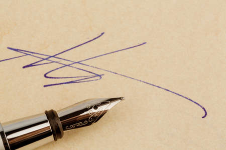 legacy: a contract or document is signed by hand with a fountain pen.