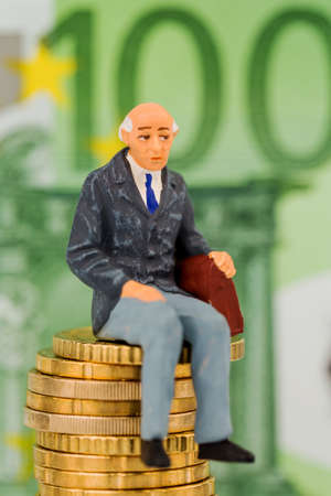 pensioners sitting on money stack, symbol photo for pension, retirement, old-age security photo