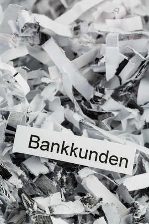 paper shredder: shredded paper tagged with bank customers, symbol photo for destruction of data, customer data, and bank secrecy Stock Photo