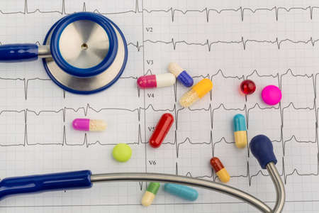 several tablets lie on an ekg. symbolic photo for diseases of the heart and circulation photo