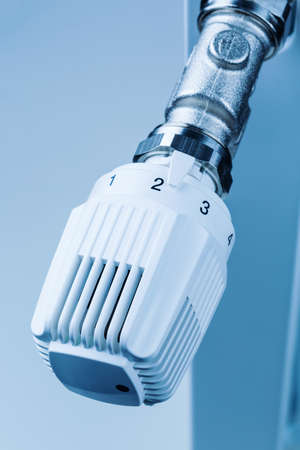 reduces: the thermostat of a radiator is slightly turned up. low room temperature reduces heating costs Stock Photo