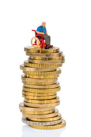 seguridad social: mujer en silla de ruedas en la pila de dinero, símbolo de fotos para la asignación de asistencia, los costos de salud Foto de archivo
