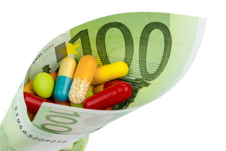 one hundred euro banknote: tablets and one hundred euro banknote symbolic photo: cost of medicine and drugs in the pharmaceutical industry