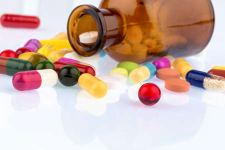 substance abuse: many tablets container. lying on a white background