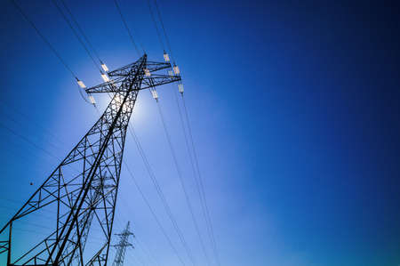 electricity grid: through a mast of a high voltage cable for electricity, the sun shines. solar energy