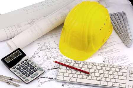 Bauplan eines Architekten mit dem Helm eines Bauarbeiters. Symbolfoto für die Finanzierung und Planung von einem neuen Haus.