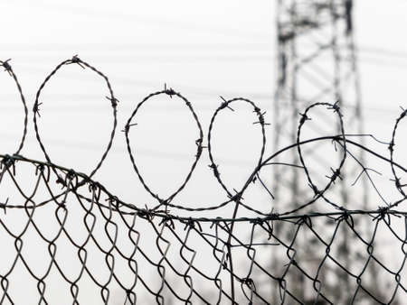 a fence is secured with barbed wire. symbolic photo for security, prison and crime. Stock Photo