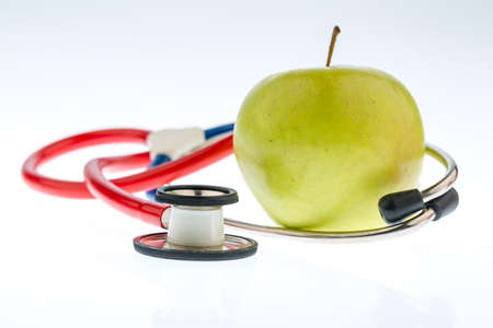stethoskope: an apple and a stethoscope on a doctor. symbolic photo for healthy and vitamin-rich diet.