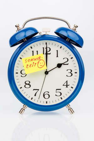 transience: an alarm clock with a note as a reminder to the uhrumstellung at summer time