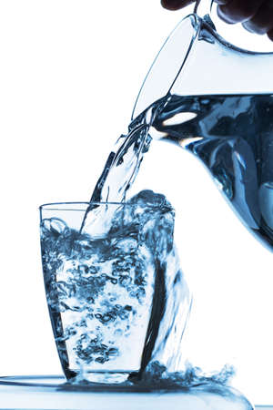 purely: pure water is emptied into a glass of water from a pitcher. fresh drinking water