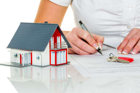 buy house: a woman signs a contract to purchase a home with a real estate agent.