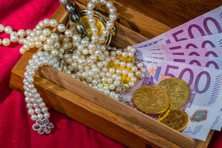 tangible: gold coins and bars with decorations on red velvet. symbolic photo for wealth, luxury, wealth tax. Stock Photo