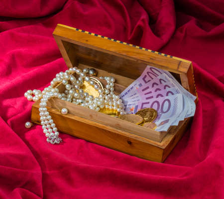 gold coins and bars with decorations on red velvet. symbolic photo for wealth, luxury, wealth tax. Stock Photo
