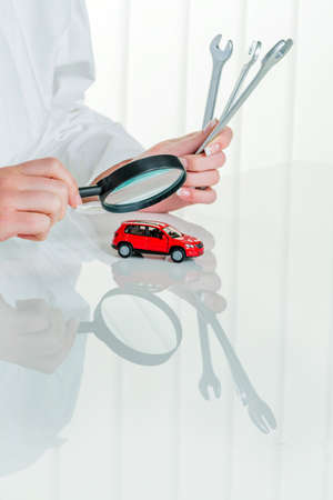 workshop service: a model of a car is examined by a doctor. symbolic photo for workshop, service and car buying.