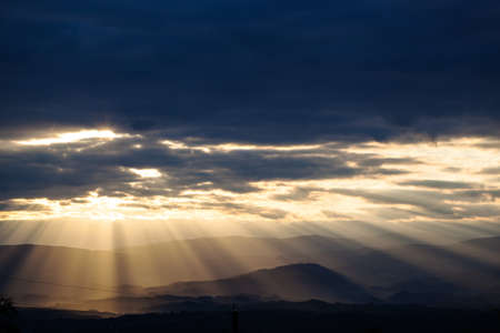 against the sun: sun rays breaking through the clouds over a mountain landscape