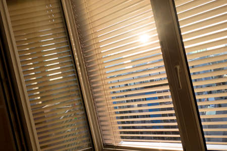 against the sun: to protect against heat and sun blinds are attached to a window. Stock Photo