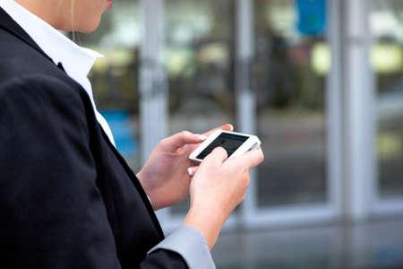 Gesch�ftsfrau schreibt �ber sms Flughafen. Roaming-Geb�hren im Ausland. Erreichbarkeit mit moderner Technik