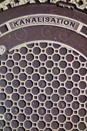derivation: the cover of a sewer on a road. Stock Photo