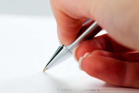 testament schreiben: eine Hand mit einem F�llfederhalter in der untrerschrift unter einem Vertrag oder Testament.