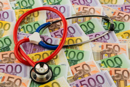 healthcare costs: stethoscope and euro bills. symbolic photo for healthcare costs and for health and medicine Stock Photo