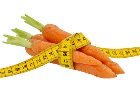 starvation: organically grown carrots with tape measure. fresh fruit and vegetables are always healthy. symbolic photo for a healthy diet. Stock Photo