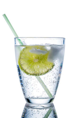 quencher: a glass of fresh drinking water and a lime. mineral water as a thirst quencher. Stock Photo
