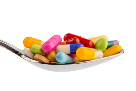 therapie: many colorful pills on a spoon. symbolic photo for tablets addiction and abuse of drugs.