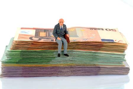 Symbolfoto für den Ruhestand und Alter, Figur eines alten Mannes sitzt auf einem Stapel von Rechnungen