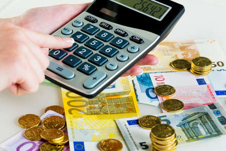 omzet: hand met rekenmachine en facturen. symbolische foto voor omzet, winst, belastingen en kosten