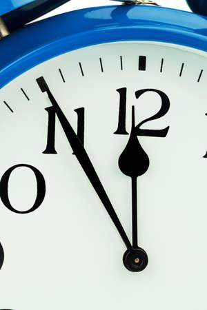 ultimatum: a blue alarm clock on white background. five to twelve Stock Photo