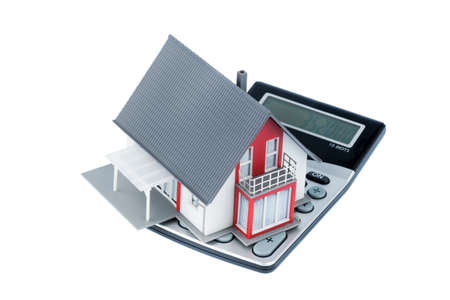 immobilien: residential building on a calculator, symbolic photo for home purchase, costs and savings