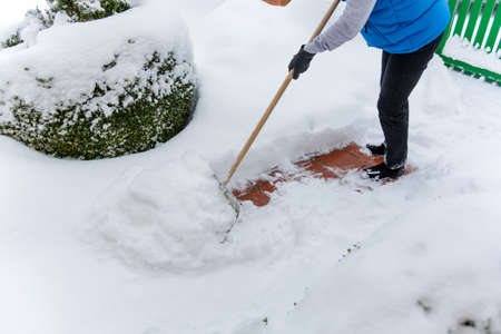 clearing: a woman shoveling the new snow from a path. onset of winter Stock Photo