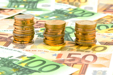 financial gains: three stacks of money coins symbol photo for financial planning, investment and interest income