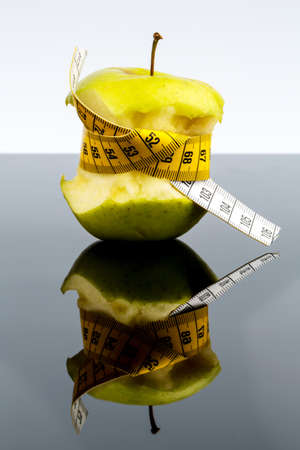 free weight: apple with a measuring tape. symbolic photo for diet and healthy, vitamin-rich diet. Stock Photo