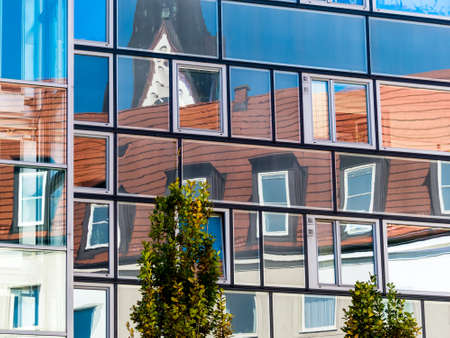 mansard: the roof extension of a residential building reflected in the glass facade of a modern office building