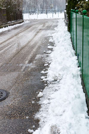 homeowners insurance: snow on sidewalk and street, symbol for accident risk and photo r?umpflicht