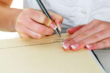 a woman signs a contract or a will with a fountain pen. photo