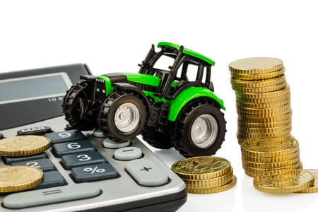reckon: farmers in agriculture have to reckon with rising costs. higher prices for feed, fertilizer and plants. tractor with coins and calculator