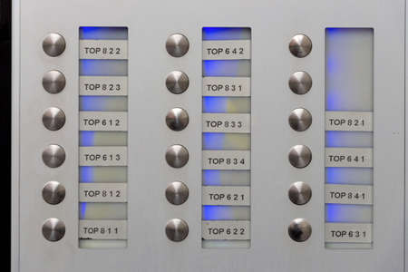 anonym: the name plates on a doorbell in a new residential house. anonymity in the big city