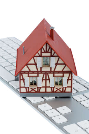residential house on keyboard symbol photo for home purchase and rental on the internet photo