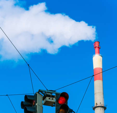 chimney of an industrial company and a red light. symbolic photo for environmental protection and ozone. photo