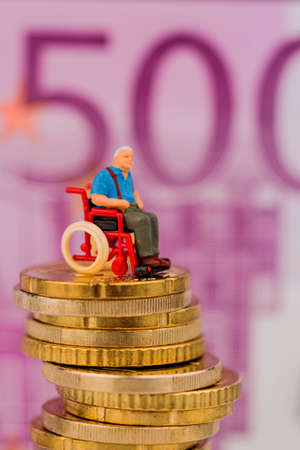 nursing allowance: woman in wheelchair on money stack, symbol photo for disability care allowance and costs