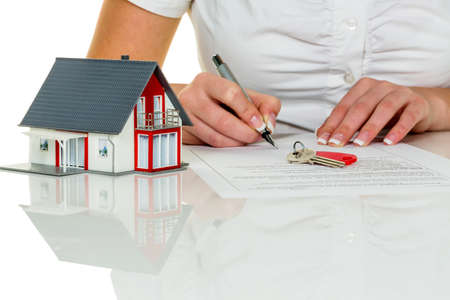 building insurance: a woman signs a contract to purchase a home with a real estate agent.