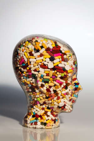 therapie: a head made of glass filled with many tablets. photo icon for drugs, abuse and addiction tablets. Stock Photo