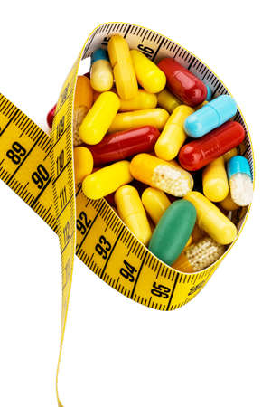supplementary: tablets and measuring tape, symbol photo for appetite suppressant, diet pills and thinness Stock Photo