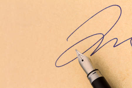 a signature and a fountain pen on yellow paper. symbolic photo for contract testament and graphology photo