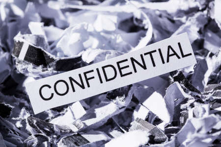 confidentiality: shredded paper tagged confidential, symbol photo for data destruction, banking secrecy and confidentiality Stock Photo